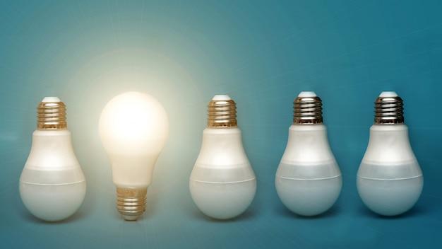 Uma lâmpada branca brilha entre as outras. idéias de conceito. se destaca entre outros. uma lâmpada brilhante brilha