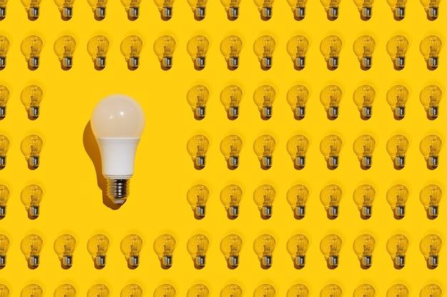 Uma lâmpada branca economizadora de energia e muitas lâmpadas incandescentes em um fundo amarelo. conceito de ideia.