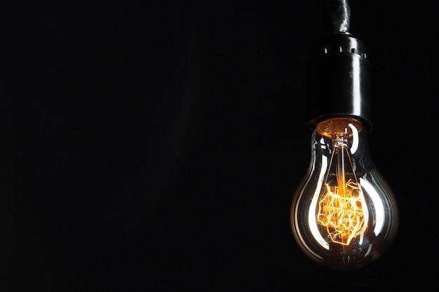 Uma lâmpada de edison clássica no escuro com espaço para texto