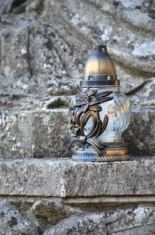 Uma lâmpada de metal fica na superfície de pedra de uma antiga cripta
