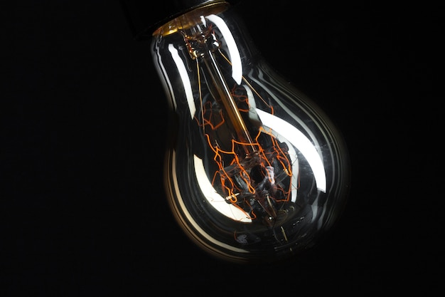 Uma lâmpada edison clássica em fundo escuro com espaço para texto