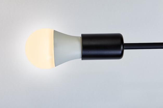 Uma lâmpada led com temperatura de cor quente de 2700 kelvin, suporte da lâmpada com lâmpada elétrica contra teto caiado.