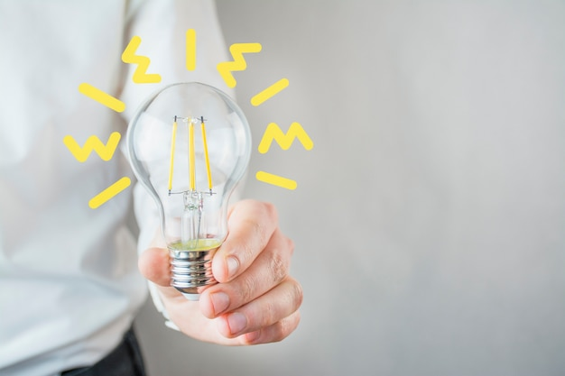 Uma lâmpada na mão de um homem em uma camisa branca. o conceito de negócio, novas idéias, inovação. ideia de negócio. homem de negocios. copie o espaço.