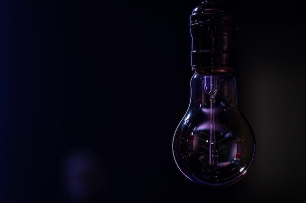 Uma lâmpada não luminosa paira no espaço da cópia de fundo desfocado escuro.