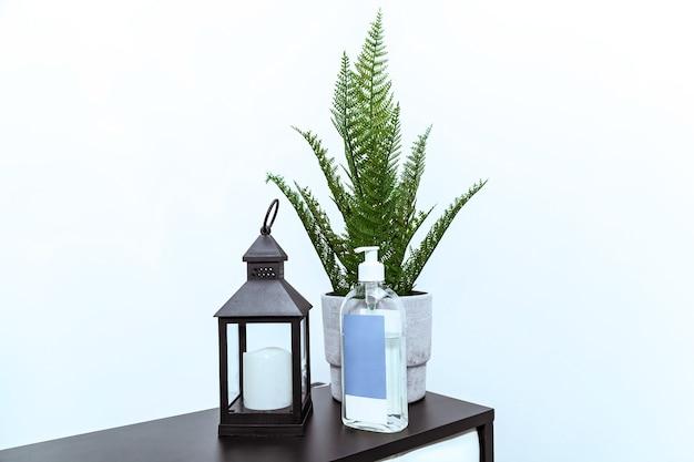 Uma lanterna com uma vela, uma samambaia verde em um vaso de flores e um frasco de desinfetante na recepção do escritório.