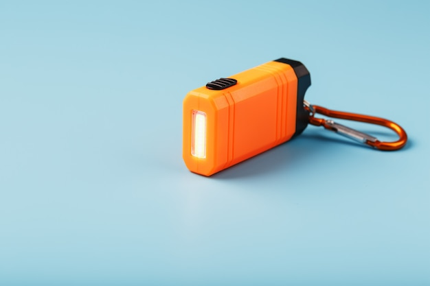 Uma lanterna led laranja com um mosquetão brilha sobre um fundo azul.
