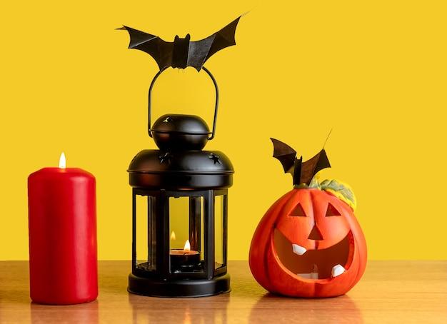 Uma lanterna negra está sobre a mesa. vela e abóbora vermelhas. um morcego de papel preto está sentado na lanterna.
