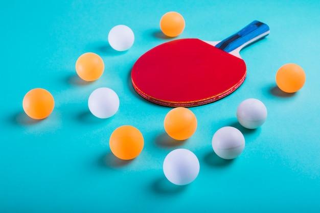 Uma laranja e bolas brancas com raquete de ping pong em fundo azul