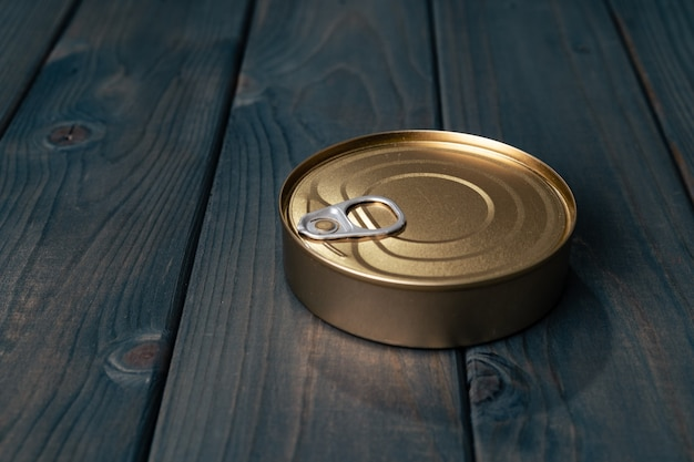 Uma lata com comida enlatada em fundo preto de madeira