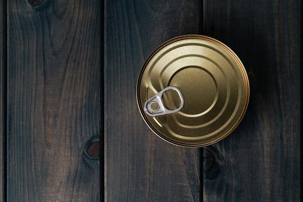 Uma lata com comida enlatada na superfície de madeira preta