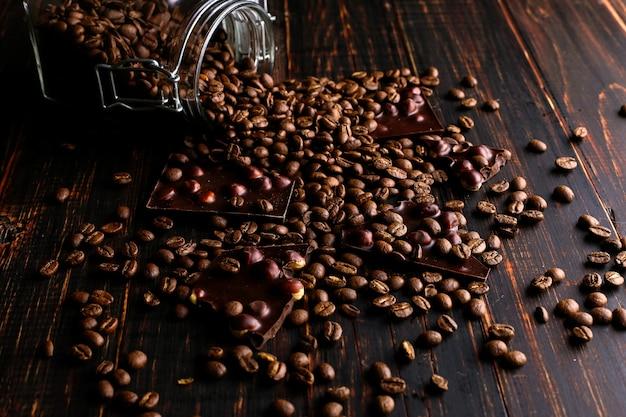 Uma lata de café, grãos espalhados e chocolate preto em uma mesa de madeira.