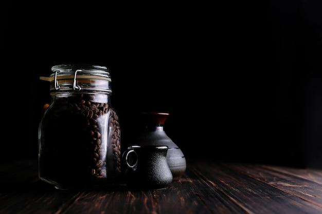 Uma lata de café, um copo e um turco em uma mesa de madeira, sobre um fundo preto.