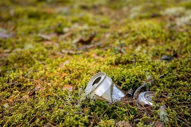 Uma lata de cerveja jogada fora em problema florestal no ambiente natural