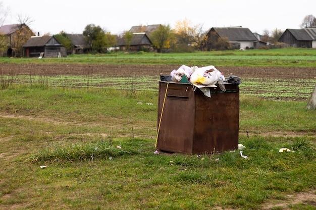 Uma lata de lixo enferrujada transbordando no campo.