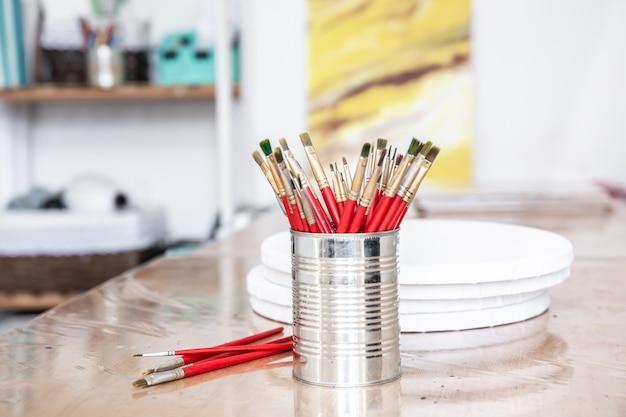 Uma lata de metal com um conjunto de pincéis para pintura em uma oficina de arte