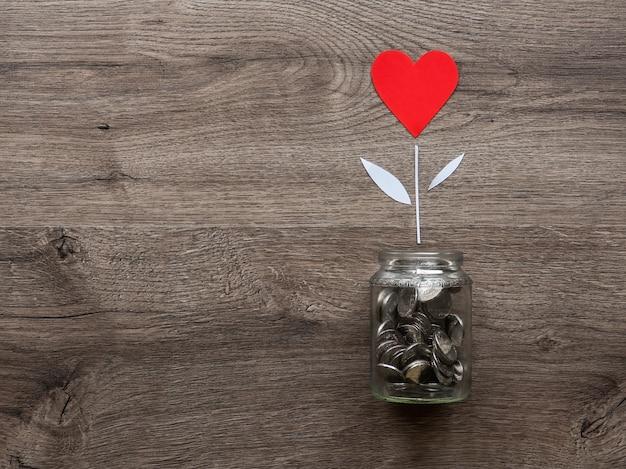 Uma lata de vidro com moedas de metal e uma flor com coração vermelho crescendo