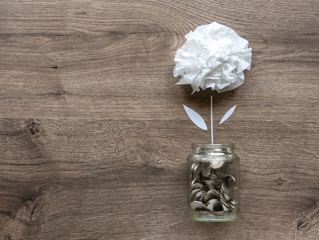 Uma lata de vidro com moedas de metal e uma flor crescendo