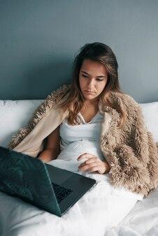 Uma latina doente na cama faz uma videochamada com um laptop para o médico