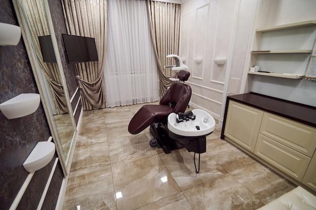 Uma lavagem de barbeiro branca e uma cadeira marrom vazia em um salão de beleza de luxo.