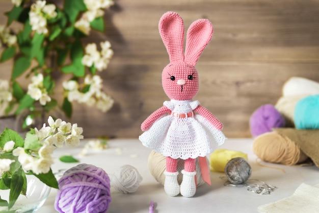 Uma lebre feita de fios de lã. brinquedo de pelúcia de malha artesanal sobre uma mesa de madeira.
