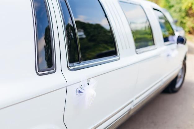 Uma limusine branca chique com maçanetas decoradas aguarda os noivos