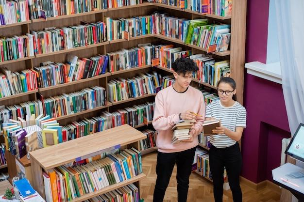 Uma linda adolescente apontando para a página de seu bloco de notas enquanto mostra notas de escola para seu colega de classe na biblioteca da faculdade