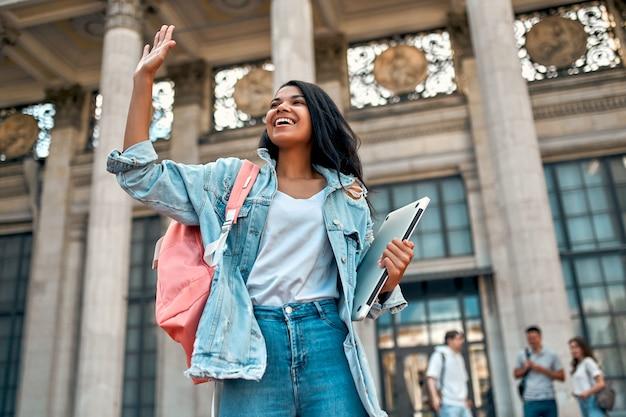 Uma linda aluna afro-americana acena com a mão e cumprimenta com uma mochila e um laptop perto do campus