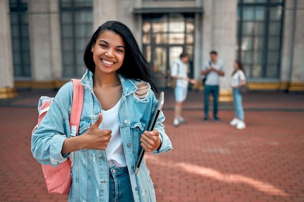 Uma linda aluna afro-americana mostra um gesto de positivo com uma mochila e um laptop perto do campus