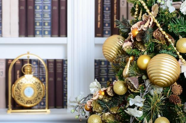 Uma linda árvore de natal decorada no fundo de uma estante com muitos livros