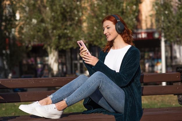 Uma linda, atraente e feliz garota ruiva caucasiana com fones de ouvido, ouvindo música e usando um smartphone enquanto está sentado em um banco.