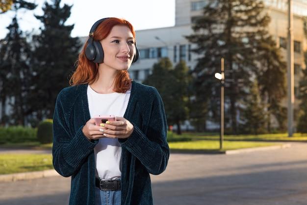 Uma linda, atraente e feliz garota ruiva caucasiana com fones de ouvido, ouvindo música e usando um smartphone.