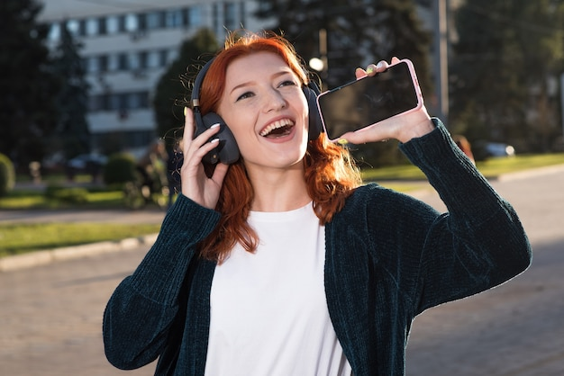 Uma linda, atraente e feliz garota ruiva caucasiana com fones de ouvido, ouvindo música, usando um smartphone e cantando uma música.