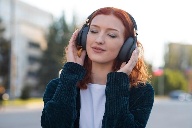 Uma linda, atraente e feliz garota ruiva caucasiana com fones de ouvido, ouvindo música.