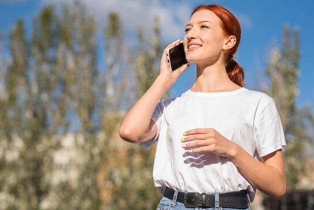 Uma linda, atraente e feliz ruiva caucasiana garota falando ao telefone. conceito autônomo.