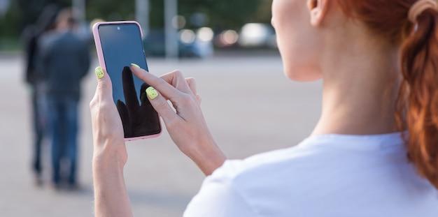 Uma linda, atraente e feliz ruiva caucasiana usando um smartphone. conceito autônomo. vista traseira.