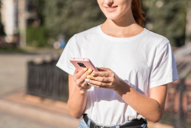 Uma linda, atraente e feliz ruiva caucasiana usando um smartphone. conceito autônomo.