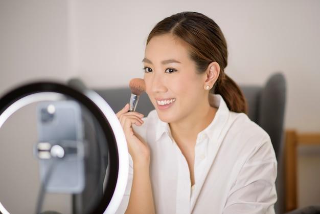 Uma linda blogueira de maquiagem asiática está transmitindo ao vivo como fazer maquiagem de rosto em casa