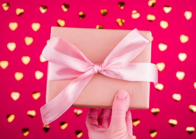 Uma linda caixa de presente com fita de cetim na mão.
