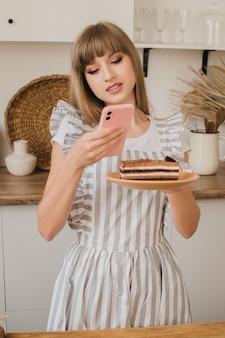 Uma linda chefe de confeitaria ou dona de casa fotografa sobremesa no telefone