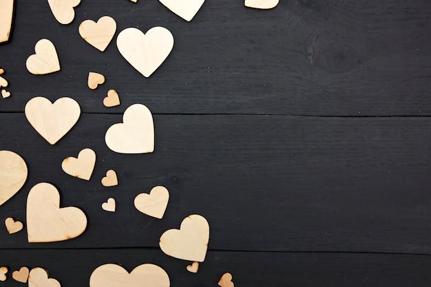 Uma linda com muitos corações de madeira na mesa escura