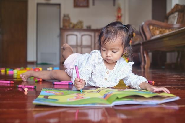 Uma linda criança asiática deitada enquanto tinge com giz de cera em um livro de artesanato com adesivo em casa