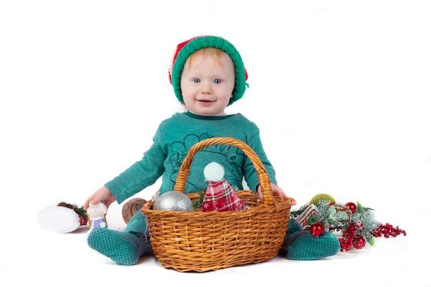 Uma linda criança de natal com uma cesta cheia de brinquedos de natal sorri. garoto engraçado com decorações para árvores de natal.