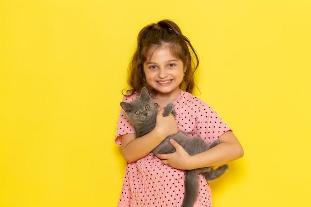 Uma linda criança de vestido rosa segurando um gatinho cinza e sorrindo