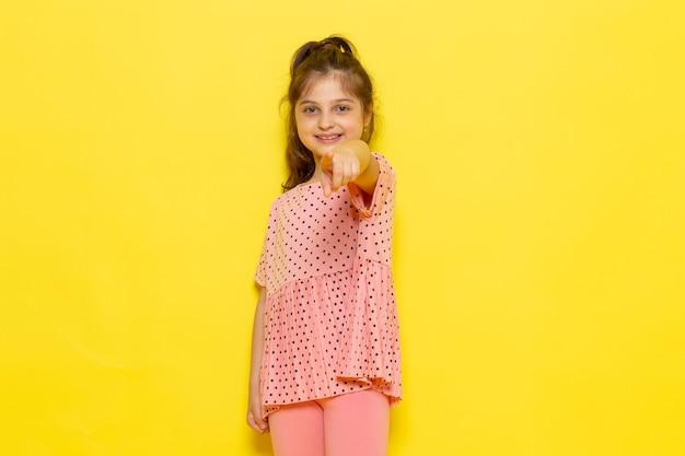 Uma linda criança de vestido rosa, sorrindo e apontando para a frente