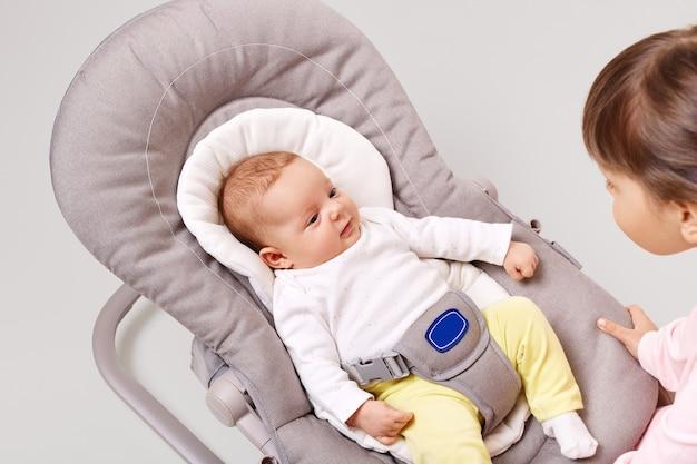 Uma linda criança recém-nascida na cadeira de balanço, olhando com expressão curiosa para a irmã