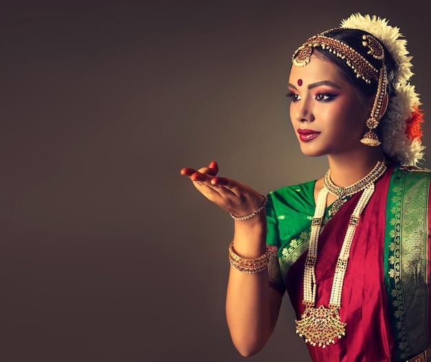 Uma linda dançarina vestida com um terno indiano tradicional está demonstrando um gesto de dança autêntico