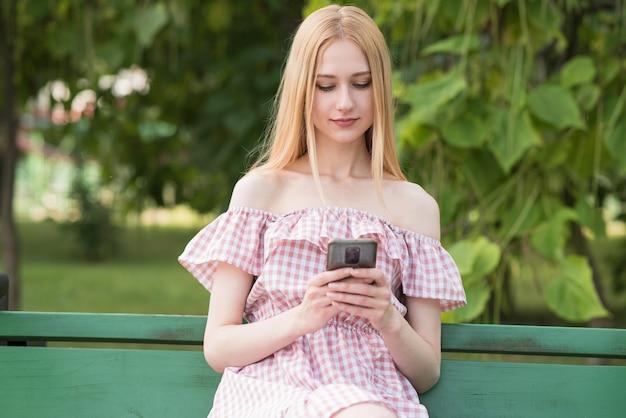 Uma linda e atraente garota loira sentada em um banco e usando um smartphone