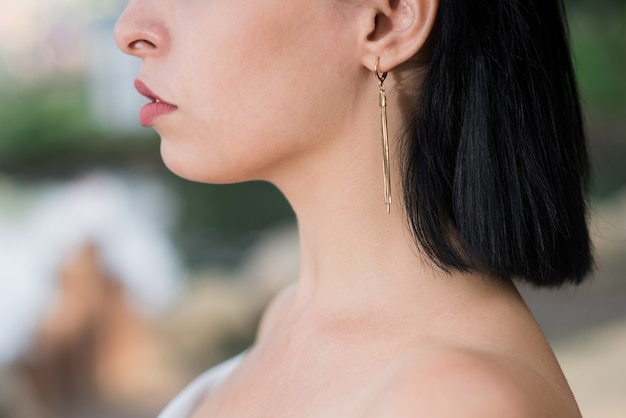 Uma linda e atraente garota morena caucasiana está usando brincos. perto de um brinco na orelha. conceito de moda.