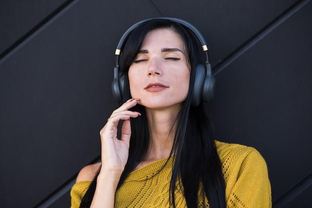 Uma linda e atraente menina morena caucasiana com uma camisola amarela, gostando de ouvir música com fones de ouvido.