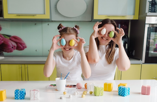 Uma linda e feliz mãe e sua filha seguram ovos coloridos perto dos olhos. o conceito de preparação do feriado para a páscoa. tradições familiares